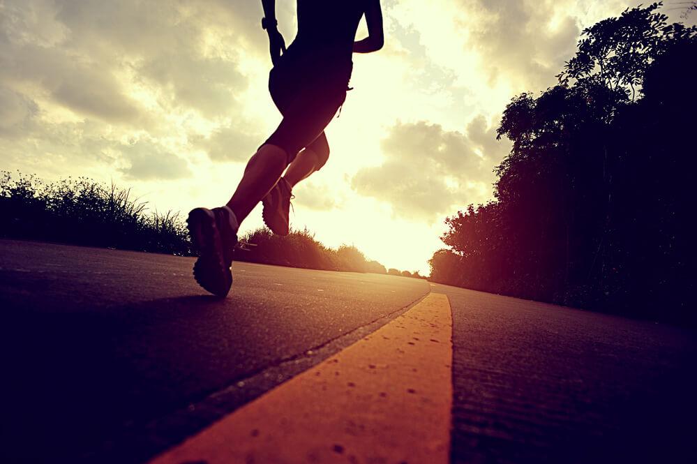 mulher que faz parte de uma assessoria esportiva correndo no asfalto